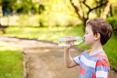 Boy drinking mineral water from the plastic bottle Stock Photos