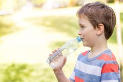 Boy drinking mineral water from the plastic bottle Royalty Free Stock Photography