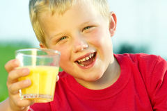 Boy drinking orange juice Royalty Free Stock Photography