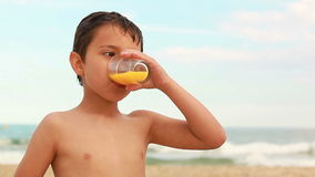 Boy drinking orange juice. On the beach