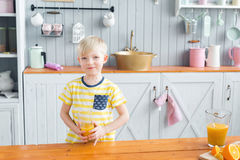 Boy drinking orange juice. Healthy food concept. holding a glass in his hand. Son and young mother in the kitchen eating Breakfast. Boy drinking orange juice stock photography