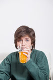 Boy drinking a oranje juice. Young boy holding a glass of orange juice Royalty Free Stock Image