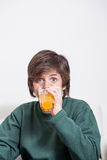 Boy drinking an oranje juice. Young boy drinking an orange juice Royalty Free Stock Photo