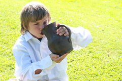 Boy drinking from a pitcher. Little boy in white shirt drinking water from a pitcher royalty free stock photo