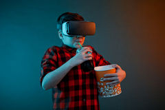 Boy drinking soda in VR helmet. Young kid drinking the soda and holding a popcorn basket wearing virtual reality headset Stock Photos
