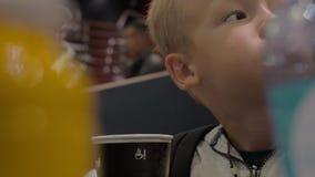 Boy drinking tea in McDonald fast food restaurant stock video footage
