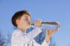 Boy drinking water. A nine years old boy drinking water from a bottle in the sun stock photography