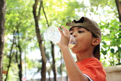 Boy Drinking Water. An Asian boy drinking water during a hot day in a park stock photos