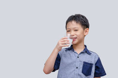 Boy drinking water. Asian boy drinking water over gray background Royalty Free Stock Images