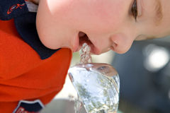 Boy drinking at water fountain. Young boy drinking from an outdoor water fountain stock image