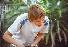 Boy drinking water from a fountain Stock Photo