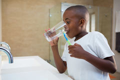 Boy drinking water from glass. While standing by sink royalty free stock photography
