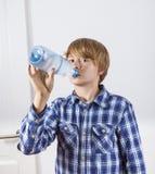 Boy drinking water out of a bottle. Cute boy drinking water out of a bottle Stock Photography