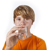 Boy drinking water out of a glass Stock Image