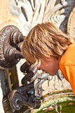 Boy drinking water on a public fountain Royalty Free Stock Photography