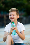 Boy drinking water. Smiling boy in elementary school age drinking water from plastic bottle outdoors royalty free stock image