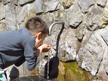 Boy drinking water at spring. In nature at outdoor park stock photos