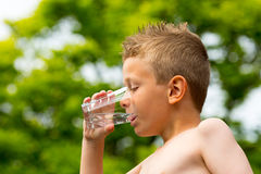 Boy drinking water. Young caucasian boy drinking from glass with fresh water outdoors during summer time stock photography