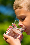 Boy drinking water. Young caucasian boy drinking from glass with fresh water outdoors during summer time stock photos