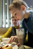 Boy drinks milk chocolate cocktail Royalty Free Stock Photos