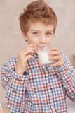 Boy drinks milk and smiles Royalty Free Stock Photo