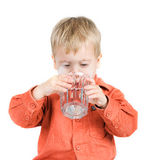 The boy drinks water. From a glass Royalty Free Stock Image