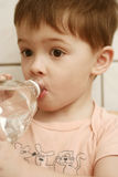 The boy drinks water from a bo. Ttle Royalty Free Stock Photo