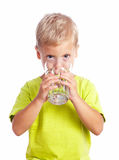 Boy drinks water from a glass cup Stock Images