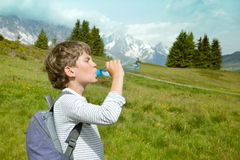 The boy drinks water on mountain walk Stock Photo