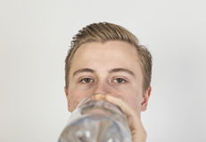 Boy drinks water out of a bottle. Cute boy drinks water out of a bottle Royalty Free Stock Image