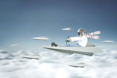 Boy drives a paper plane. Picture of a little boy wearing an adventure helmet and driving a paper plane on the sky Royalty Free Stock Image