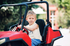 Boy drives a toy electric car Royalty Free Stock Image