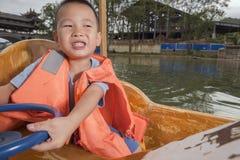 Boy driving boat Stock Image
