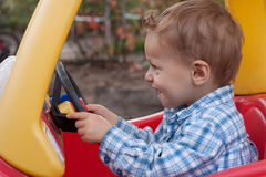 Boy Driving Car. Young two year old toddler boy pretending to drive his toy car Royalty Free Stock Image