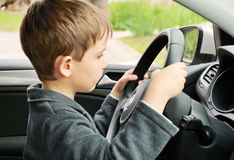 Boy driving a car and looking at the way Stock Images