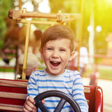 Boy driving a car on merry-go-round Stock Photography