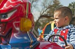 Boy driving car toy in the amusement park. Closeup Stock Photos