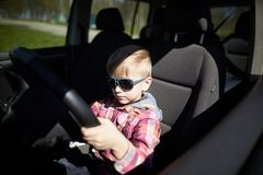 Boy driving fathers car. Little cute boy driving fathers car at springtime Stock Photos