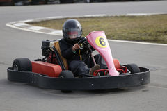 Boy is driving Go-kart car with speed in a playground racing track. Stock Photography