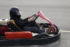 Boy is driving Go-kart car with speed in a playground racing track. Royalty Free Stock Photography