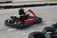 Boy is driving Go-kart car with speed in a playground racing track. Royalty Free Stock Photo