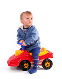Boy driving a red toy car. Little blond boy driving a red toy car royalty free stock photography
