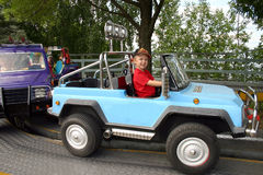 Boy driving toy car. Preschool boy driving car in amusemant park Stock Photo