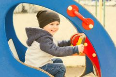 Boy driving a toy car on the Playground. Boy 3 years old sitting in a toy car on the Playground Royalty Free Stock Images