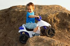 Boy driving toy quad on terrain Royalty Free Stock Photo