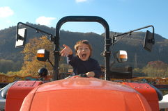 Boy driving a tractor. Boy having fun on driving a tractor Stock Images