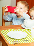 Boy drooling eating breakfast playing with mobile phone Stock Photo