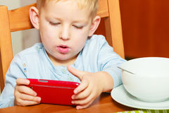 Boy drooling eating breakfast playing with mobile phone Royalty Free Stock Photography