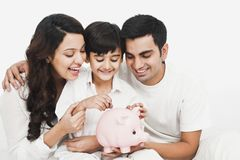 Boy droping coin in the piggy bank. With his parents smiling Stock Photography