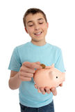 Boy dropping coin into money box Stock Photos